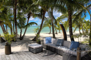 resort in the Bahamas with a pathway to the beach and lounging section surrounded by palm trees