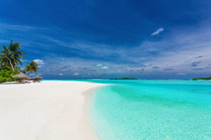 crystal blue waters on sandy white beaches with clear blue skies and clouds and palm trees
