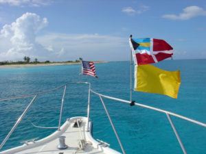 a boat facing the islands in turquoise waters with flag posted on the front