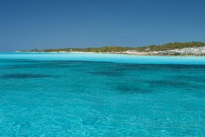 clear turquoise waters off of the coast of Mayaguana under a perfectly clear blue sky with the island in the distance