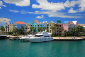 colorful buildings of hotels with a dock in the back equipped with several yachts rested on turquoise, calm waters